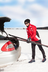 Woman with car during unloading of cross-country skis