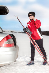 Woman with car and cross-country skis