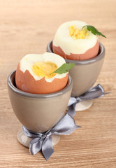 Boiled eggs in egg cups, on wooden table