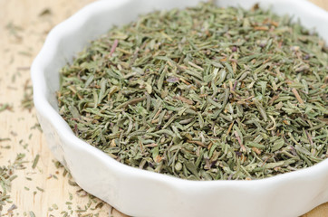 dried thyme in a white bowl, selective focus, closeup