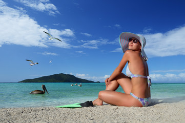 Young woman relaxing on the beach enjoying the flying birds