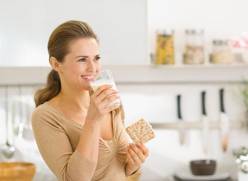 Young woman eating crisp bread with milk