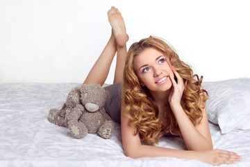 Beautiful happy smiling young woman in bed at home