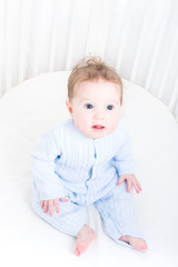 Funny baby sitting in a white round crib