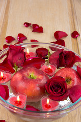 Valentine apple with rose petals and heart candles
