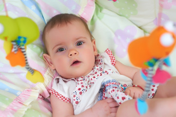 Little cute baby girl lying in crib with toy