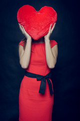 pretty woman squeezing Valentine heart in her arms