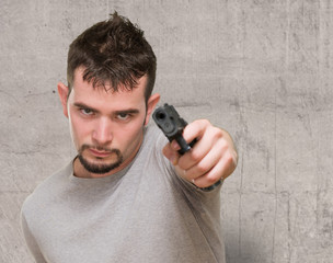 Young man with a gun looking serious
