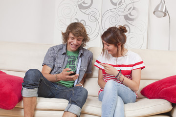 teen couple commenting a fun message on the phone