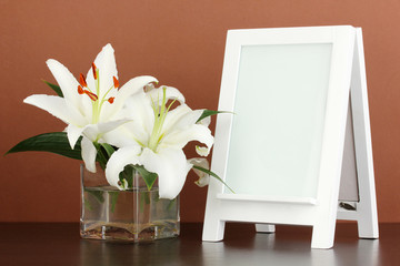 White photo frame for home decoration on brown background