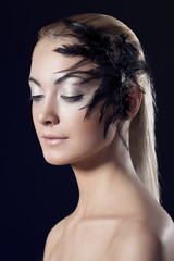 girl turned of three quarters with feathered accessory