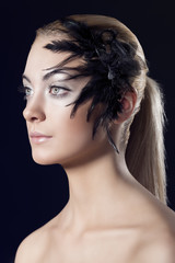 girl with feathered accessory looks at right