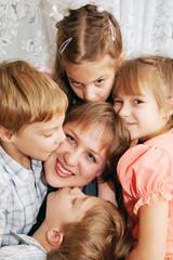 Four children kissing mother. Family concept