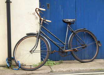 Rusty old bicycle chained to a drainpipe.