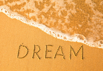 Dream, text written by hand in sand on a beach.