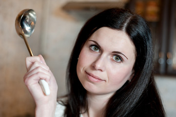 young brunette with a serving spoon in kitchen