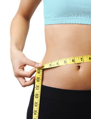 Young woman measuring her perfect waist. Close up