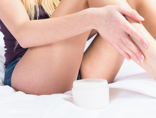 Pretty woman applying creme to her legs