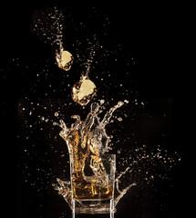 Glass of whiskey with splash, isolated on black background