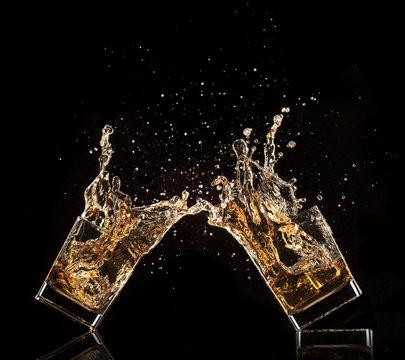 Glasses of whiskey with splash, isolated on black background