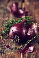 Red onions with thyme on wooden background