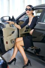 Elegant woman with long legs in car