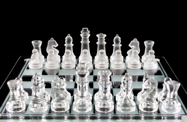 Glass chess pieces on chess board isolated in black