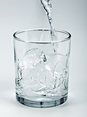 Water flowing onto ice in glass
