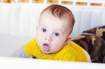 The surprised baby lies on a stomach in a bed