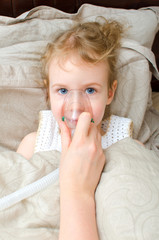Little girl lying in bed with inhalator mask on the face
