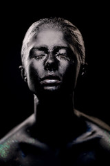 girl in black paint on dark background