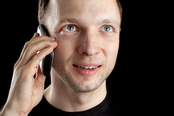 Young Caucasian man talks on mobile phone