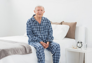 Elderly man sitting on his bed