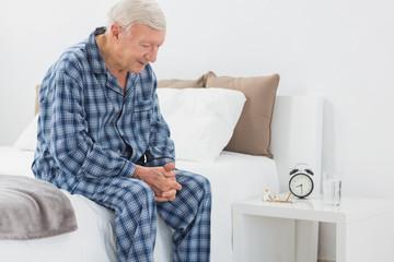 Elderly man sitting on the bed
