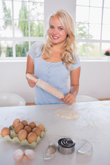 Smiling woman with a rolling pin and ingredients