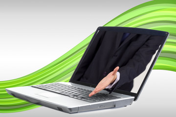 Businessman reaching out from laptop for handshake