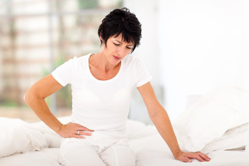 mature woman sitting on bed and having stomach ache