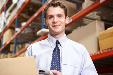 Businessman Scanning Package In Warehouse