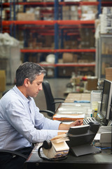 Manager Working At Desk In Warehouse