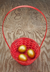 Golden Easter eggs in a red basket. On a wooden texture.