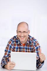 mann mit laptop zeigt daumen hoch