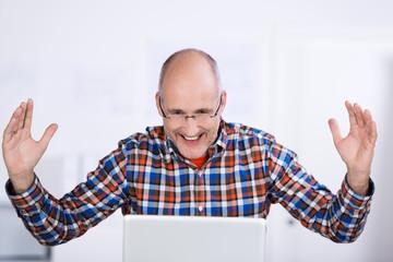 mann schaut auf laptop und jubelt
