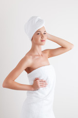 Beautiful blonde female model in bath towel on white background