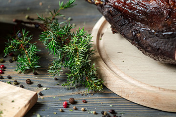 Closeup of juniper and fresh sliced smoked ham