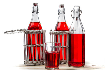 Vintage bottles with red juice on white old table