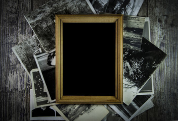 Photo frame with lots of photos lying on an old table