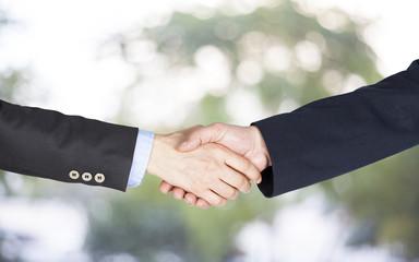 Hand shake on green background