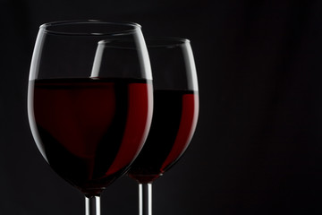 Two glassed of red wine isolated on black background