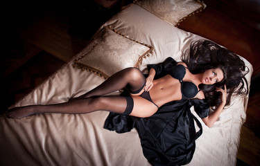 sexy brunette young woman wearing black lingerie in bed