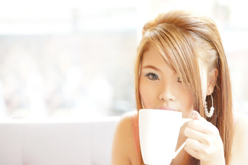 Closeup beautiful woman sitting in cafe holding and drinking cof